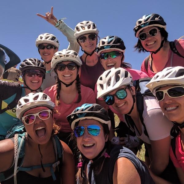 Group shot of 10 women with bike helmets and sunglasses on smiling at camera.