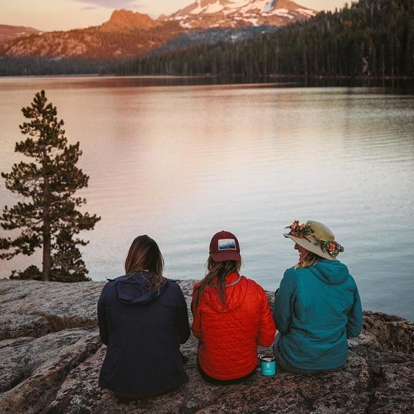 Three women sitting on a flat rock with their backs to the camera looking out at a vast lake in a mountain setting.
