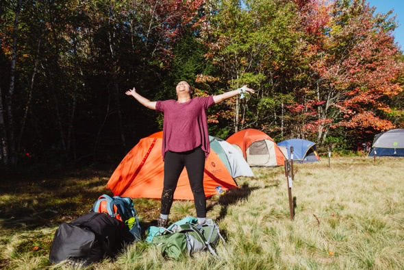 Woman with arms outstretched facing the sun at campsite with tents in the background. She stands in a grassy field amidst autumn-colored trees.