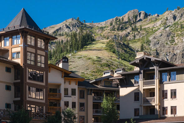 A blue sky peers above a rocky, green mountain range with a resort in the foreground. The resort is a multi-story structure with balconies and windows.