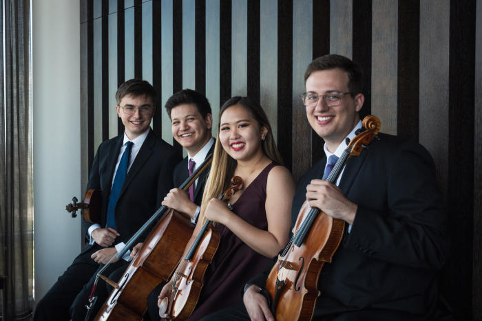 Photograph of the four members of the Balourdet Quartet, smiling, seated with their instruments.